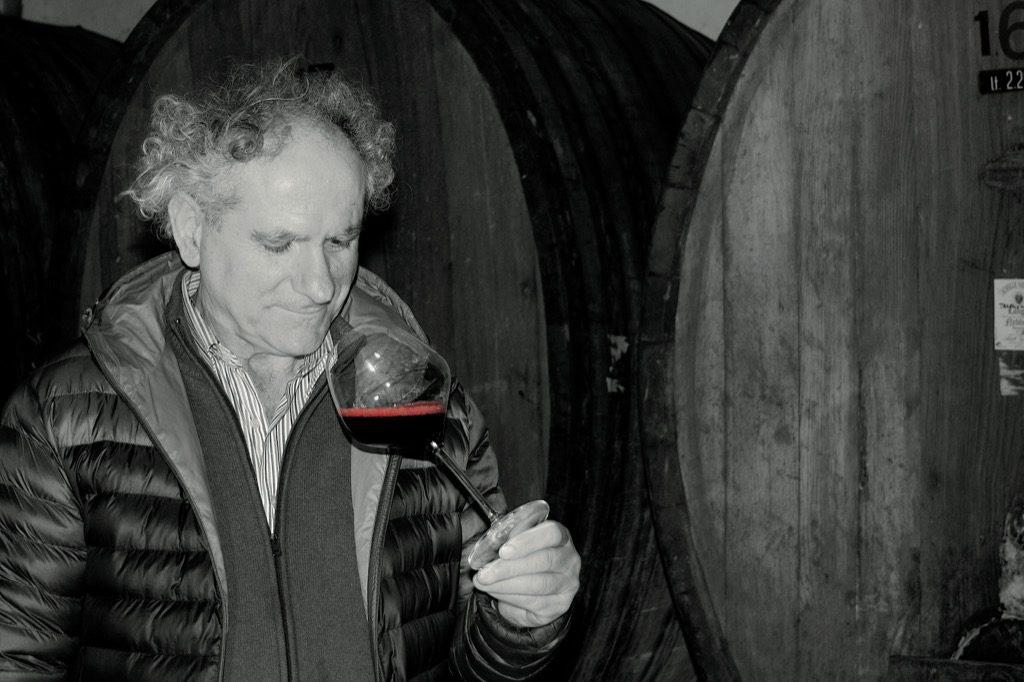 Achille Viglione in cantina con botti e un calice di vino rosso