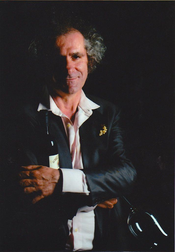 Achille Viglione in una foto vintage con bottiglia di vino e bicchiere